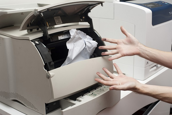 Frustrated person with ink on their hands trying to clear a paper jamb in an office printer