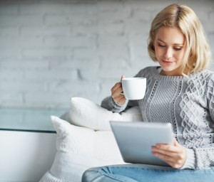 A pretty young woman using a digital tablet while enjoying a cup of coffee