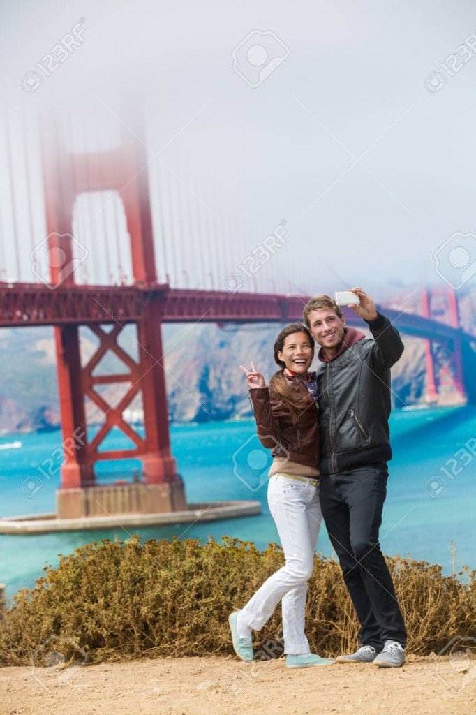 Tourists couple taking selfie photo in San Francisco by Golden Gate Bridge. Interracial young modern couple using smart phone by famous amaerican landmark. Asian woman, Caucasian man.