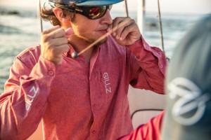 Man wearing GILLZ fishing shirt, hat, and sunglasses preparing the line on his fishing reel
