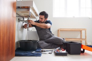 Male Plumber Working To Fix Leaking Sink In Home Bathroom