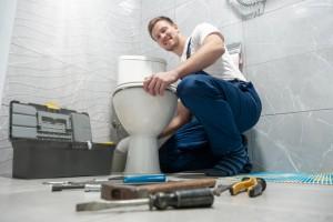 smiling man plumber in uniform repairing toilet bowl using instrument kit looks happy professional repair service.