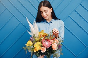 Florist with flowers. Woman makes a bouquet. Girl on a blue background