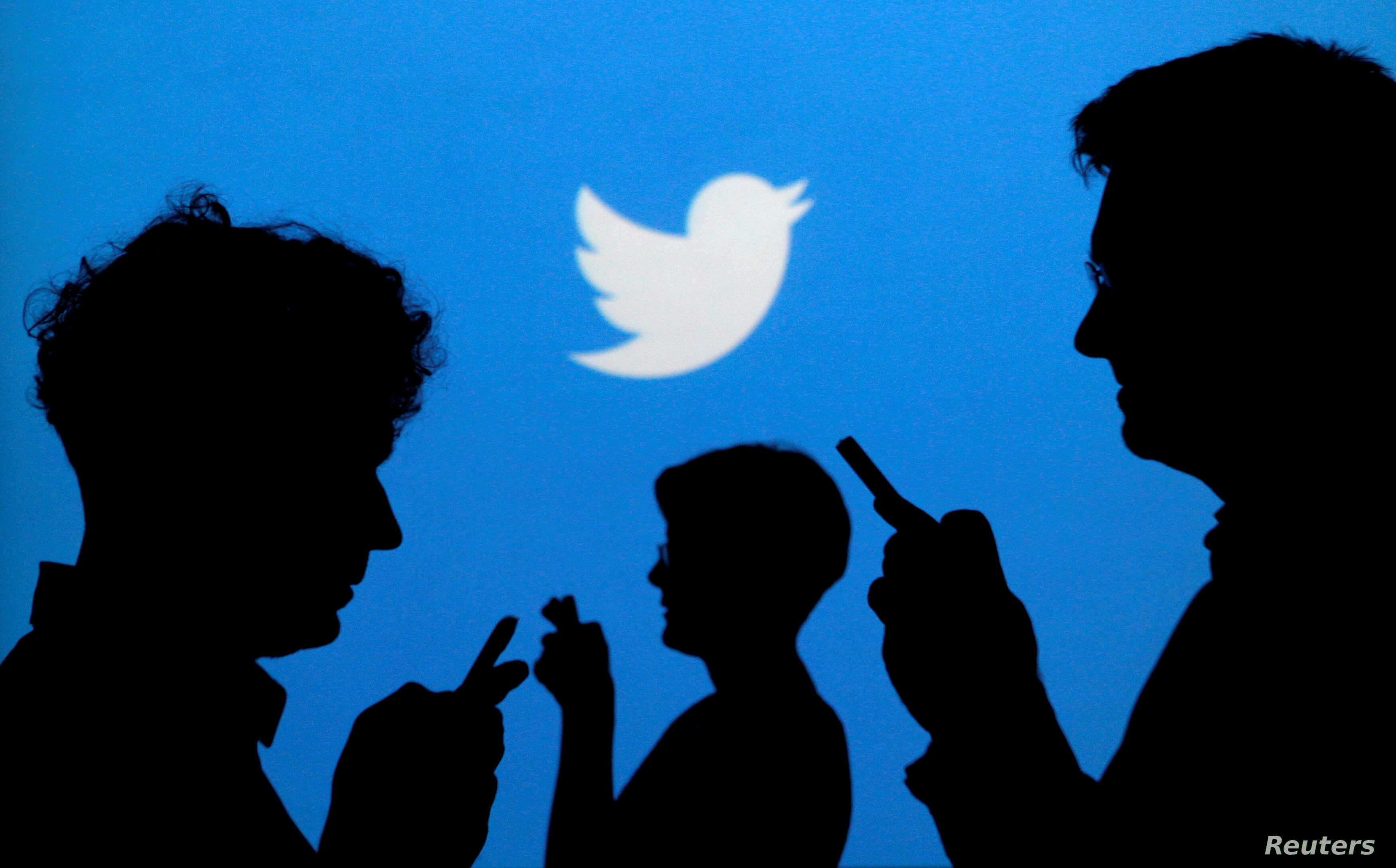 FILE PHOTO: People holding mobile phones are silhouetted against a backdrop projected with the Twitter logo in this illustration picture taken September 27, 2013. REUTERS/Kacper Pempel/Illustration/File Photo - S1AEUIXLWVAA