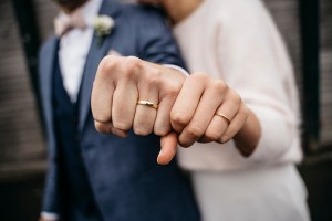Newlywed couple showing their golden wedding rings