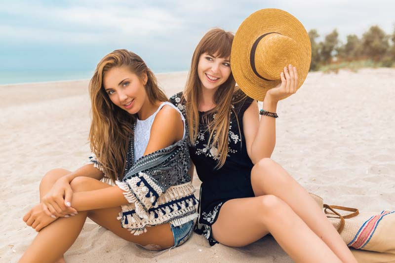 young hipster beautiful women on vacation on tropical beach, stylish summer outfit, smiling happy, fashion trend, black white hippie style, trendy accessories, straw hat, friends having fun together