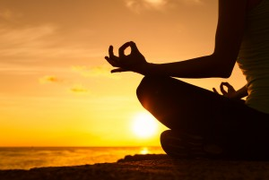 Female meditating overlooking the beautiful sunset. Healthy mind body and spirit concept.