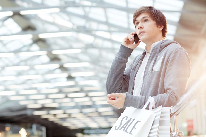 Guy in casualwear carrying paperbags and talking on smartphone in the mall during sale