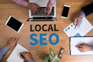 Local SEO Concep Business team hands at work with financial reports and a laptop, top view