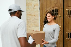 Home Delivery. Courier Delivering Package To Client. Smiling Woman Receiving Box From Delivery Man Near Door. High Resolution