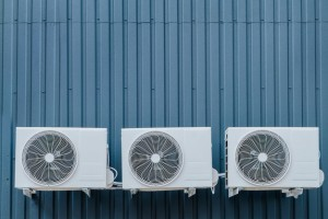 three-air-conditioner-outdoor-units-blue-wall-copy-space_134216-207